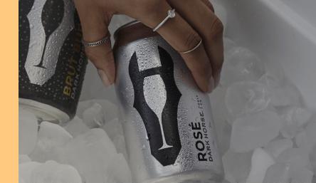 Fundo do vídeo, mulher com anéis na mão retirando uma lata do Dark Horse de dentro da caixa com gelo