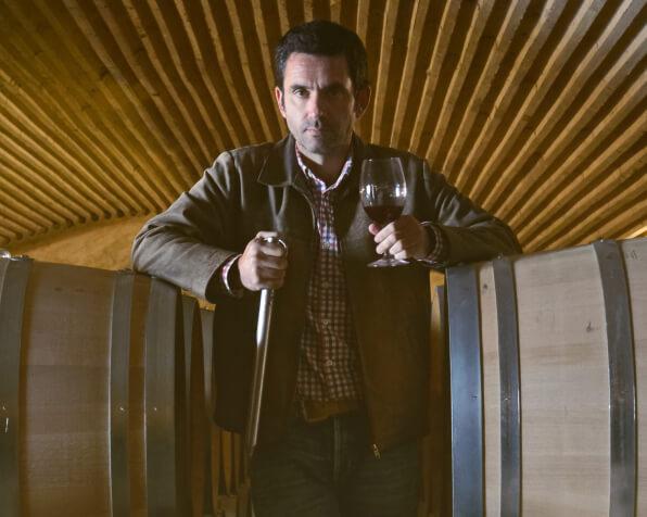 Foto do enólogo apoiado em 2 barris de vinho com uma taça na mão