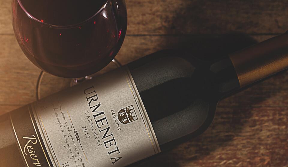 Foto de uma garrafa de urmeneta reserva tinto e uma taça com vinho.